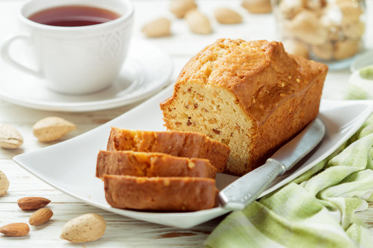 Sliced pound cake with almonds on the cutting Board. Homemade cake with nuts and honey.  Delicacy snack for tea