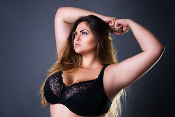 Plus size sexy model in black bra, fat woman with big natural breast on gray studio background, overweight female body