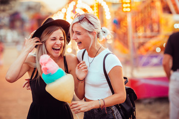 Papiers peints Attraction parc Shot of happy female friends in amusement park eating cotton candy. Two young women enjoying a day at amusement park.