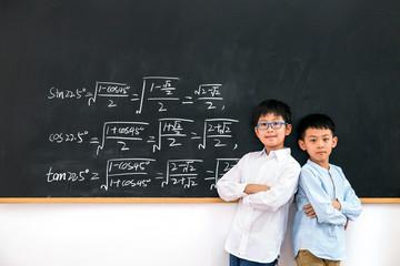 Primary school boy standing in front of the blackboard