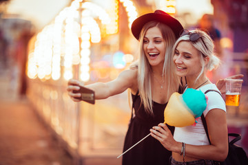 Acrylic Prints Amusement Park Happy female friends in amusement park eating cotton candy and taking selfie.Two young women enjoying a day at amusement park.
