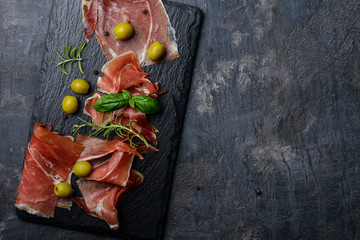 Meat plate, thin slices  of prosciutto or spanish jamon with olives on  stone cutting board, top view, copy space