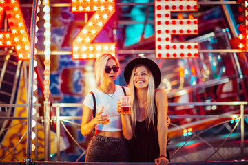 Poster Amusement Park Happy female friends in amusement park drinking beer. Two young women enjoying night at amusement park.