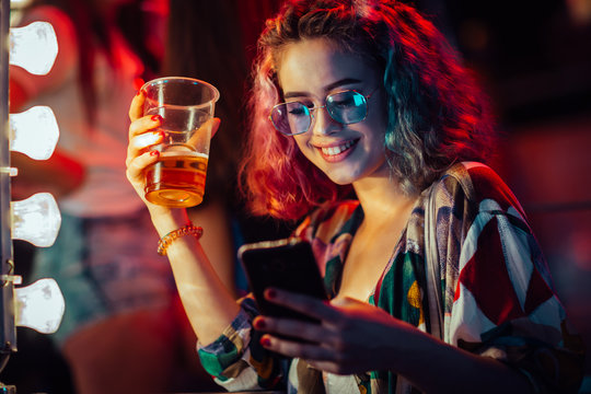 Young woman at the festival drinking beer and using mobile phone