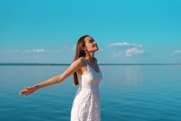 Portrait of a young woman in a white dress with open hands breathing clean sea air on the shore, fresh air, freedom, ecology