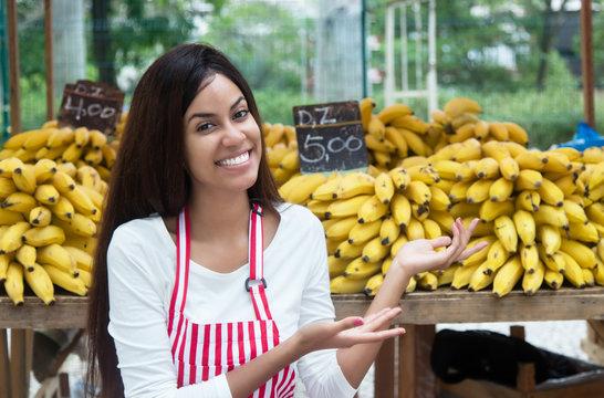 Latin american saleswoman at farmers market presenting bananas