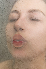 Beautiful woman with closed eyes kisses glass in the shower
