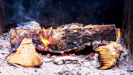 Burning pieces of wood with smoke and red hot embers.