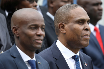 Haiti's President Moise and PM Ceant attend to the national anthem in the gardens of the National Palace during the inauguration ceremony in Port-au-Prince