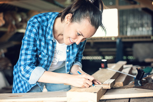 side view of smiling female carpenter to mark on a wooden Board pencil band saw cut