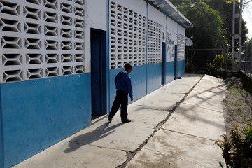 A kid walks past a classroom on the first day of school, in Caucagua