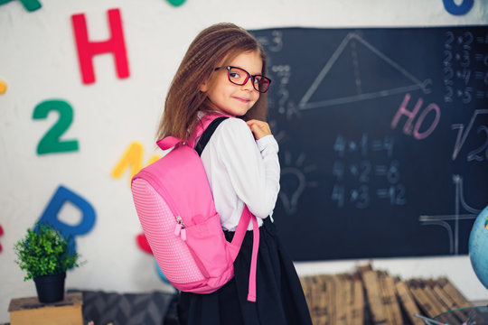 Little girl with a pink school backpack. The concept of school, study, education, friendship, childhood.