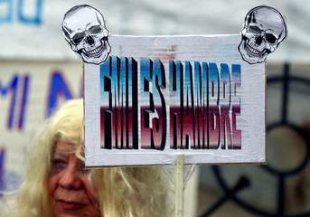 A woman holds up a sign during a protest against the government's austerity measures outside the Congress in Buenos Aires