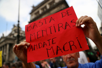 A man holds up a sign during a protest against the government's austerity measures outside the Congress in Buenos Aires
