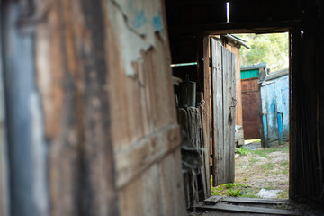 Open door of an old rotten wooden shed