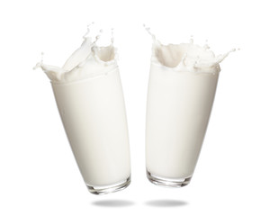 Couple milk splashing out of glass isolated on white background.
