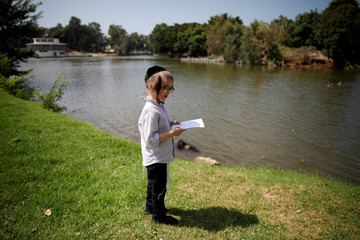 An ultra-Orthodox Jewish boy performs the Tashlich ritual ahead of Yom Kippur in Ramat Gan, Israel