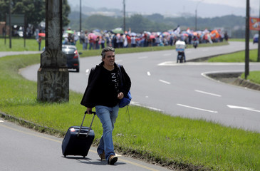 Public workers block the street giving access to Juan Santamaria Airport during an indefinite strike against the tax proposal in Alajuela