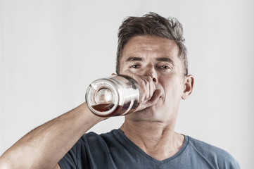 Senior man drinking alcohol from bottle on gray background