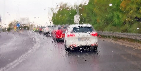 Driving a car in the rain and storm in heavy traffic. View through a windshield with rain drops during driving a car. Shallow depth of field.