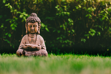 Recess Fitting Buddha Beautiful, wooden Buddha in a garden on a green grass. Representation of buddha produced in wood
