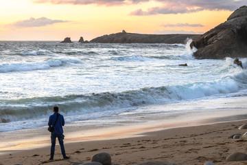 un homme en contre jour au bord d'une plage avec de grosses vagues au coucher de soleil