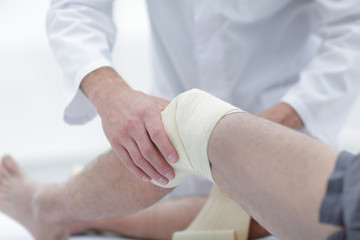 Doctor treats wound on the patient's leg in a clinic room
