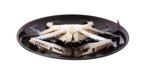 raw crab on a black plate isolated on white background.