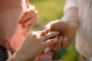 Man making a proposal to his girlfriend outdoors in the park. Man putting the engagement ring on the womans finger. Close up groom and bride hands.