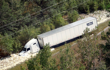 A tractor trailer sits on its side after being washed over Route 301 from flood waters caused by Hurricane Florence near Dillon, South Carolina