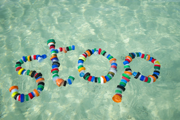 'stop' spelled out on the sand using plastic bottle caps collected floating in the sea at Miami beach, a message for people to act on pollution