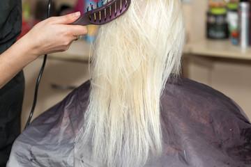 hairdresser dries hair