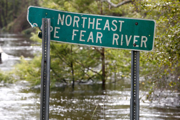 Floodwaters rise to engulf trees normally on the banks of the Northeast Cape Fear River as a battered sign identifies the river after Hurricane Florence in Burgaw, North Carolina