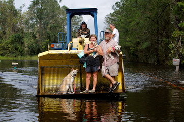A resident transports evacuees and their pets in the bucket of his tractor as the Northeast Cape Fear River breaks its banks during flooding after Hurricane Florence in Burgaw, North Carolina