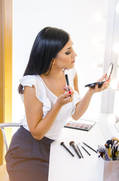 Beautiful dark hair girl in front of mirror putting on makeup