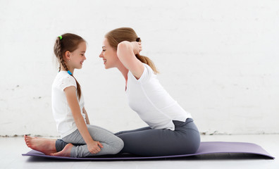 mother with child practicing yoga in lotus pose .