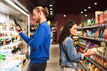 Young thoughtful couple standing back to back choosing products while spending time in modern supermarket