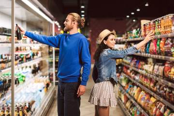 Young smiling guy choosing beer while pretty girl near choosing chip in supermarket