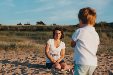 Pregnant Mother And Her Little Boy At The Beach At Sunset