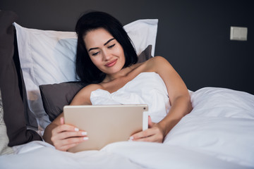 Woman Relaxing On Bed Using Digital Tablet For Video Call