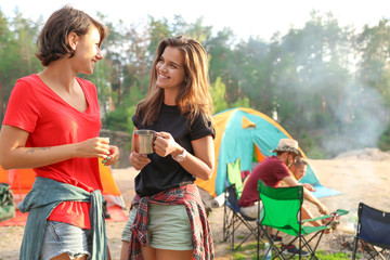 Young women near camping tent in wilderness