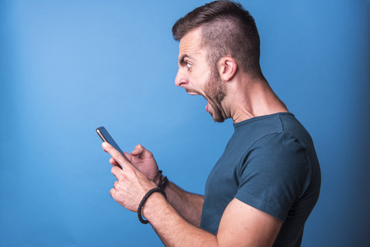 Angry, enraged man shouting at his cellphone, profile from the side, blue background