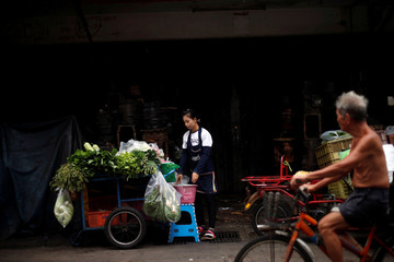 A street vendor sells vegetables in a street in Bangkok