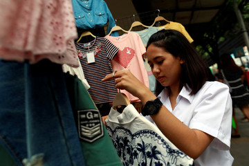 A university student holds clothes as she helps her parents who are street vendors in a street in Bangkok
