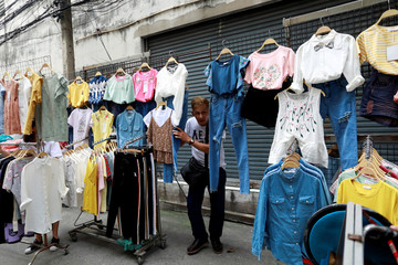 A street vendor holds his clothes when police take action on a street in Bangkok