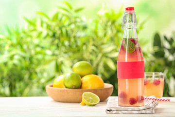 Bottle with natural lemonade on table against blurred background