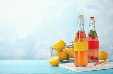 Bottles with natural lemonade on table against color background