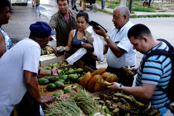 People buy vegetables on a street in Havana