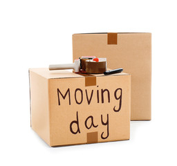Moving boxes, marker and adhesive tape dispenser on white background