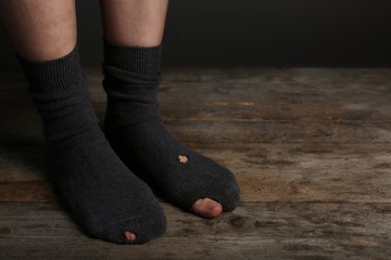 Poor person in shabby socks on wooden floor, closeup